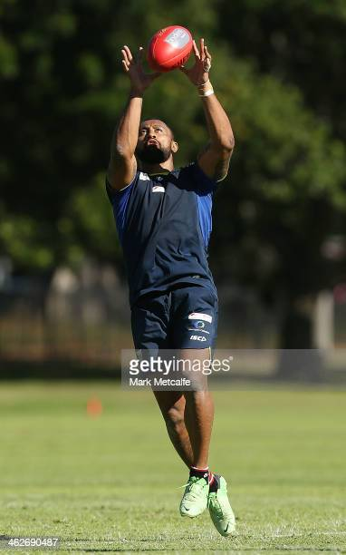 Roy Asotasi of the Warrington Wolves catches an AFL ball during a Sydney Swans AFL preseason training session at Lakeside Oval on January 15 2014 in...