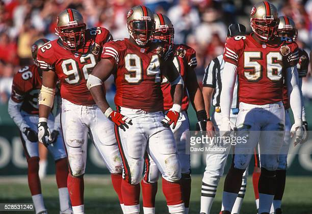 Roy Barker Dana Stubblefield and Chris Doleman of the San Francisco 49ers await the next play during a National Football League game against the...