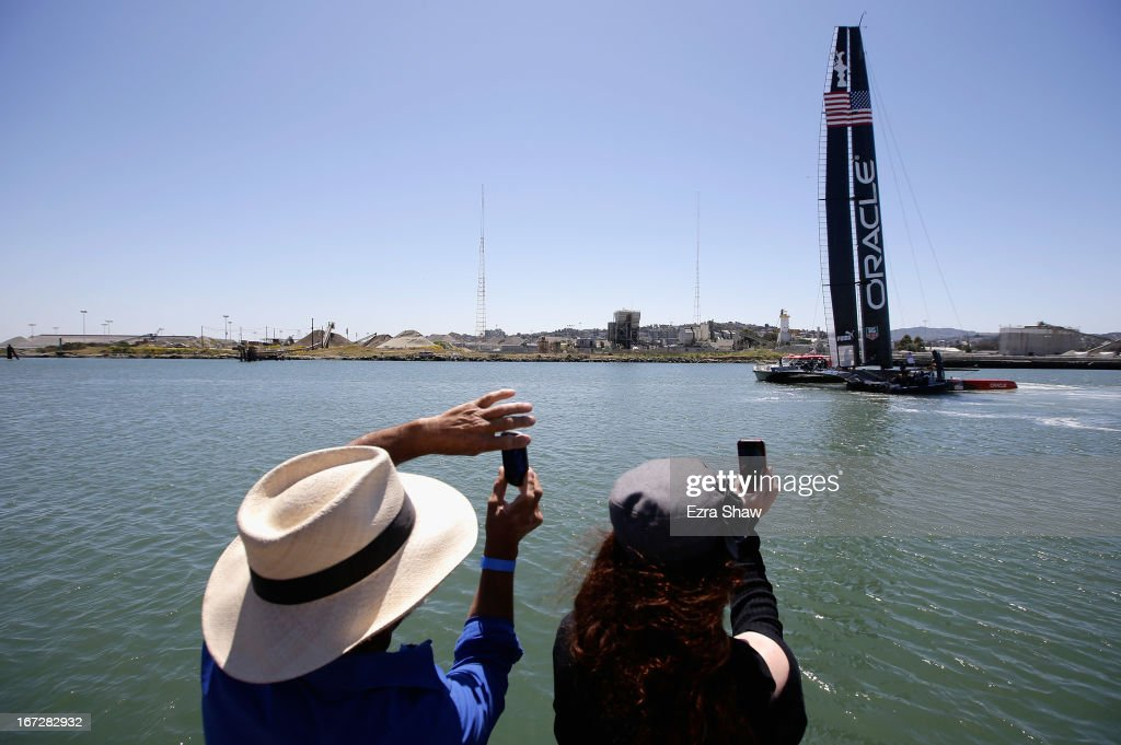 Roy Cano (L) of Sausalito and Erika Redding of San Francisco take pictures of the new Oracle Team USA AC72 as it leaves the dock for the first time on April 23, 2013 in San Francisco, California. This yacht will be used in this year's America Cup Finals, which will be held in San Francisco Bay between September 7-22.