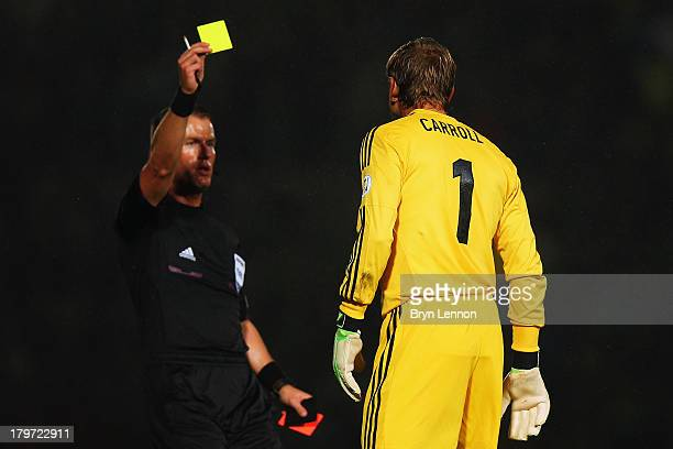 Roy Carroll of Northern Ireland receives a yellow card from referee Danny Makkelie during the FIFA 2014 World Cup Qualifying Group F match between...