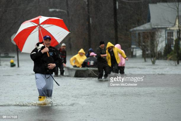 Roy Casey carries dog Buddy from his flooded neighborhood on Moore and Perkins Street March 30 2010 as the Pawtuxet River crests in Cranston Rhode...