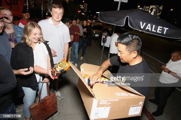 Roy Choi hands out Cheetos to guests waiting in line at The Flamin Hot Spot Cheetos new limitedtime restaurant with a menu inspired by chef Roy Choi...