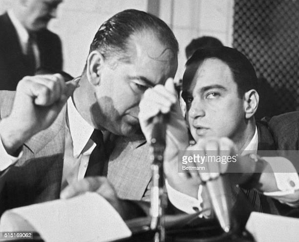 Roy Cohn covers up both microphones as he whispers to Senator Joseph McCarthy while Army Secretary Robert Stevens testifies before the Senate...