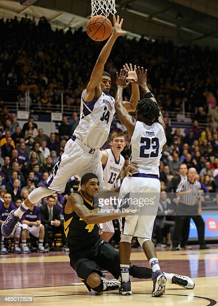 Roy Devyn Marble of the Iowa Hawkeyes hits the floor after shooting against Sanjay Lumpkin and JerShon Cobb of the Northwestern Wildcats at WelshRyan...