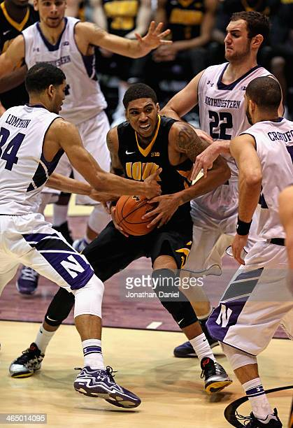 Roy Devyn Marble of the Iowa Hawkeyes is pressured by Sanjay Lumpkin Alex Olah and Drew Crawford of the Northwestern Wildcats at WelshRyan Arena on...