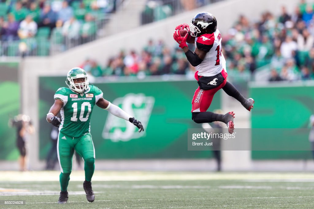 Roy Finch #14 of the Calgary Stampeders goes high to make a catch in front of Henoc Muamba #10 of the Saskatchewan Roughriders in the game between the Calgary Stampeders and Saskatchewan Roughriders at Mosaic Stadium on September 24, 2017 in Regina, Canada.