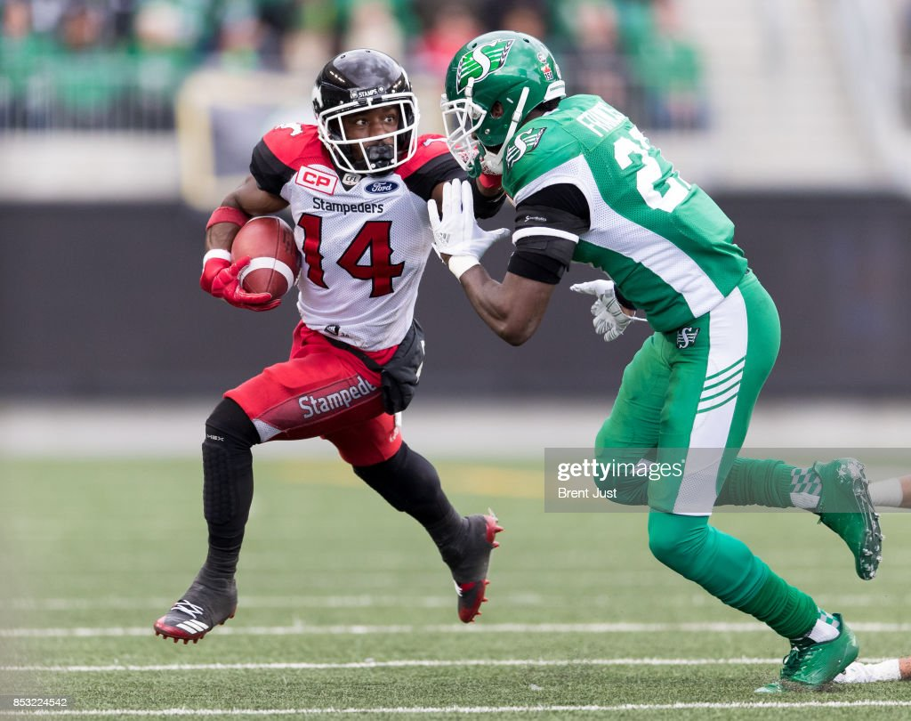 Roy Finch #14 of the Calgary Stampeders tries to avoid Otha Foster III #20 of the Saskatchewan Roughriders in the game between the Calgary Stampeders and Saskatchewan Roughriders at Mosaic Stadium on September 24, 2017 in Regina, Canada.