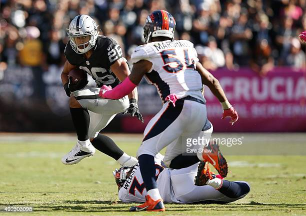 Roy Helu of the Oakland Raiders tries to avoid the tackle from Kayvon Webster of the Denver Broncos and Brandon Marshall of the Denver Broncos in the...