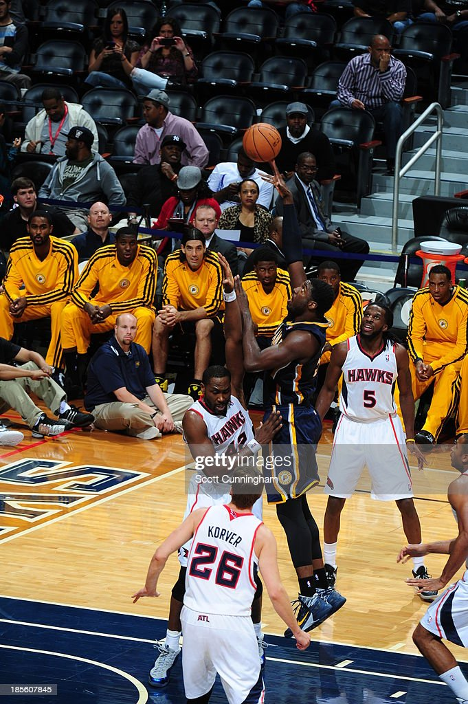 Roy Hibbert #55 of the Indiana Pacers shoots the ball against Elton Brand #42 and DeMarre Carroll #5 of the Atlanta Hawks on October 22, 2013 at Philips Arena in Atlanta, Georgia.