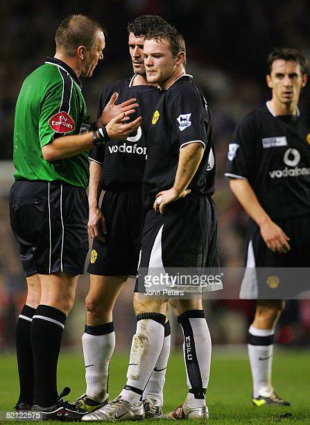 Roy Keane and Wayne Rooney of Manchester United talk to referee Graham Poll during the Barclays Premiership match between Arsenal and Manchester...