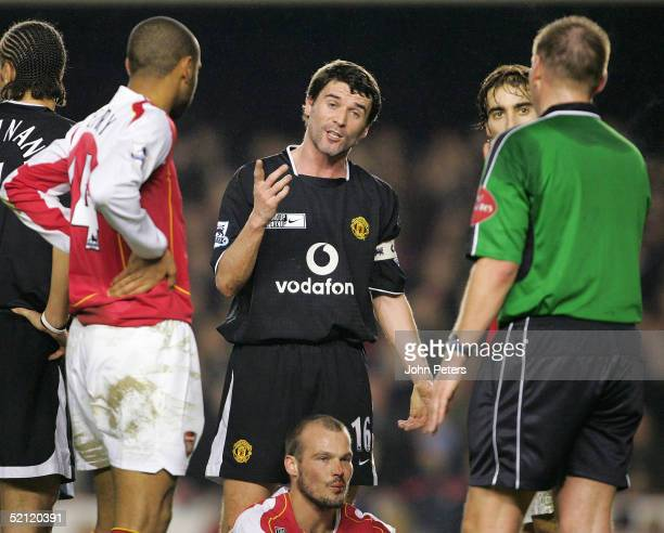 Roy Keane of Manchester United speaks with referee Graham Poll while Freddie Ljungberg of Arsenal sits with a bloody nose during the Barclays...