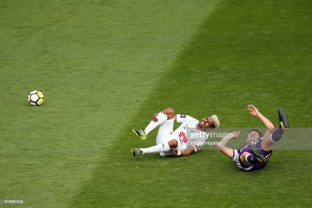 Roy Krishna of the Phoenix and Alex Grant of the Glory react after colliding during the round six A-League match between the Wellington Phoenix and the Perth Glory at Westpac Stadium on November 12, 2017 in Wellington, New Zealand.