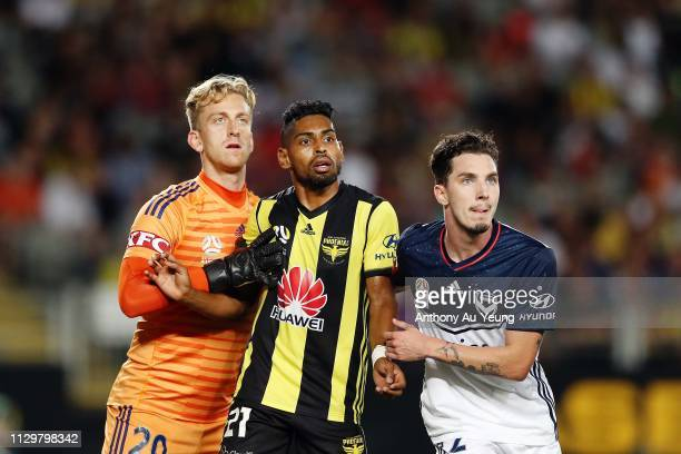 Roy Krishna of the Phoenix is tightly marked by goal keeper Lawrence Thomas and Storm Roux of the Victory during the ALeague match between the...
