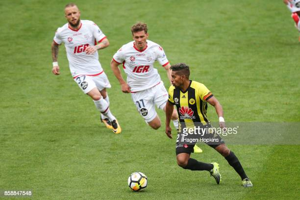 Roy Krishna of the Phoenix makes a break from Johan Absalonsen and Nikola Mileusnic of Adelaide United during the round one ALeague match between...