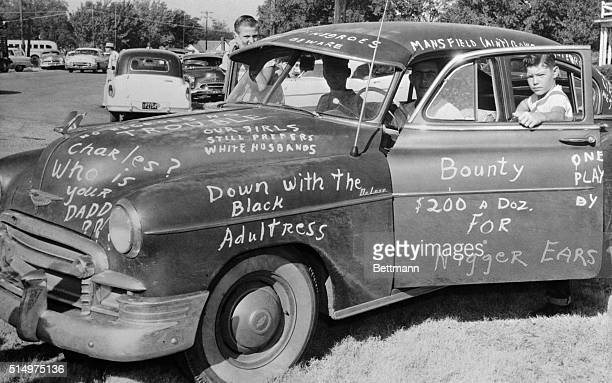 Roy Lee Howlett stands beside a car painted with signs protesting Negro students entry into Mansfield High School the car was placed at the entrance...