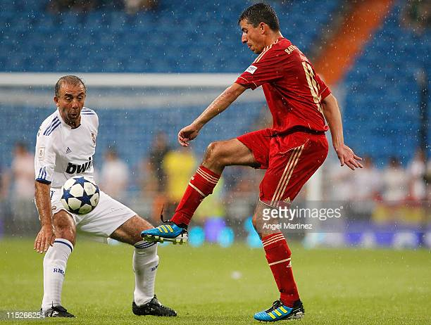 Roy Makaay of Bayern Muenchen is challenged by Rafael Garcia Cortes of Real Madrid during the Corazon Classic Match between Allstars Real Madrid and...