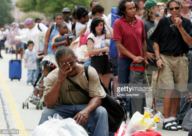 Roy Marigny wipes his forehead in the heat while waiting for the New Orleans Superdome to open as an emergency shelter ahead of Hurricane Katrina...