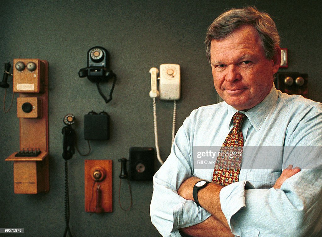 Roy Neel, President of the US Telecom Association, poses in front of antique telephones in the lobby of his office.