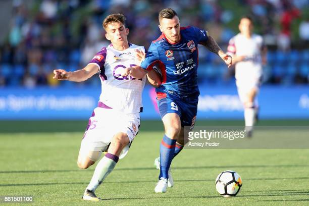 Roy O'Donovan of the Jets contests the ball against Jacob Poscoliero of Perth Glory during the round two ALeague match between the Newcastle Jets and...