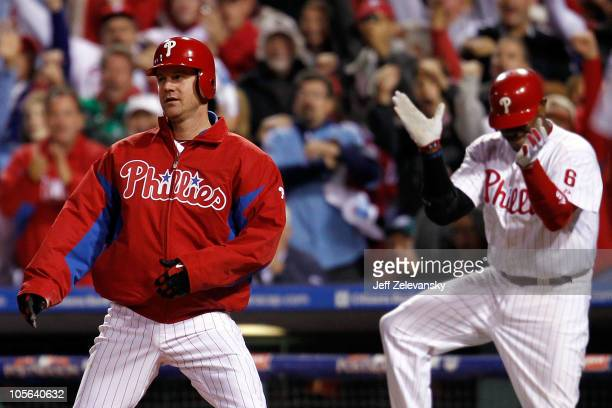 Roy Oswalt of the Philadelphia Phillies reacts as does teammate Ryan Howard after Oswalt slides home safely before the tag of Buster Posey of the San...