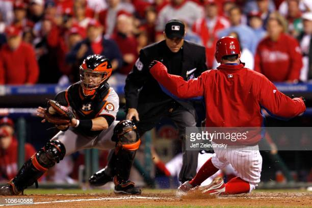 Roy Oswalt of the Philadelphia Phillies slides home safely before the tag of Buster Posey of the San Francisco Giants in in the seventh inning of...