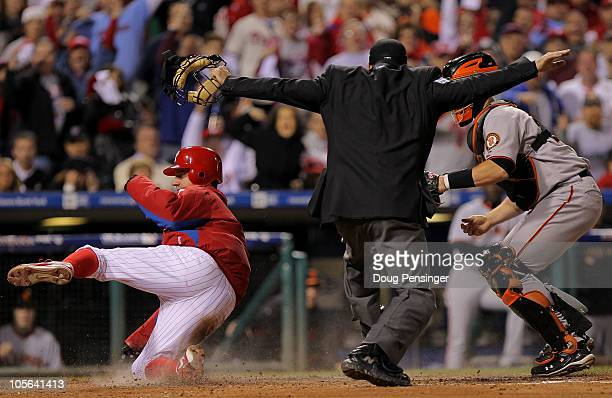 Roy Oswalt of the Philadelphia Phillies slides home safely before the tag of Buster Posey of the San Francisco Giants in the seventh inning of Game...