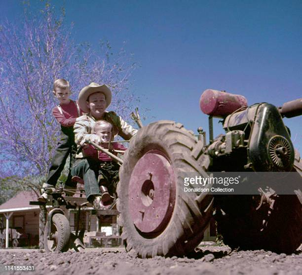 Roy Rogers and sons ride a tractor at home in 1958
