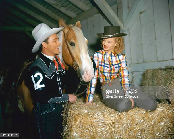 Roy Rogers US actor and singer wearing a white cowboy hat red neckerchief and western shirt posing beside his palomino horse Trigger and his wife...