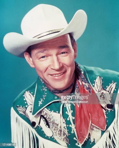 Roy Rogers US actor and singer wearing a white cowboy hat red neckerchief and fringed western shirt in a studio portrait against a blue background...