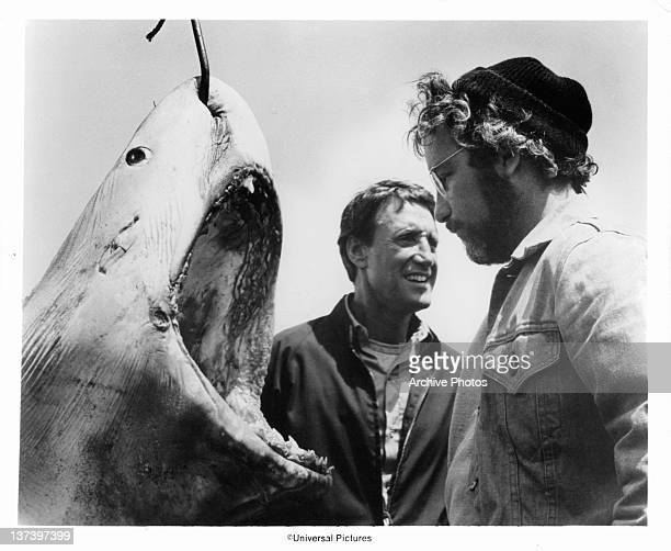 Roy Scheider and Richard Dreyfuss stand next to a giant man eating Great White Shark with a hook piercing through it in a scene from the film 'Jaws'...