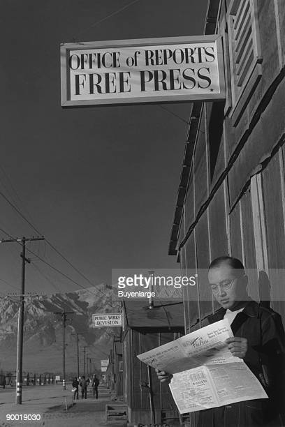 Roy Takeno reads a copy of the Manzanar Free Press in front of the newspaper office mountains in the background Ansel Easton Adams was an American...