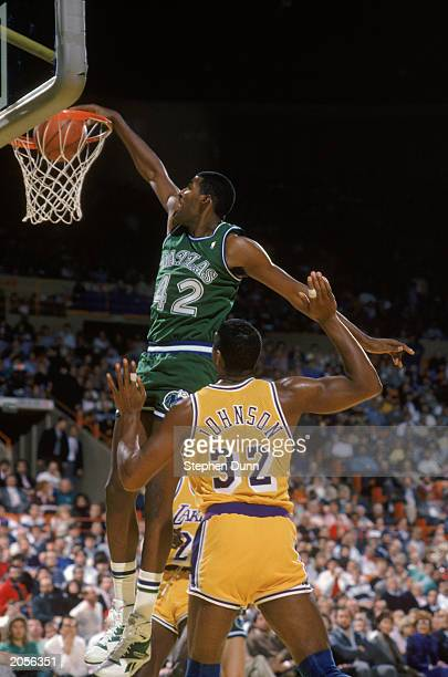 Roy Tarpley of the Dallas Mavericks dunks the ball past Earvin 'Magic' Johnson of the Los Angeles Lakers during the NBA game at the Great Western...