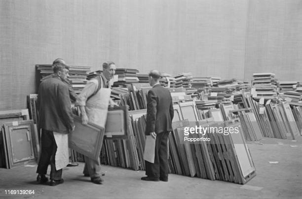 Royal Academy porters carry recently submitted paintings from stacks to be put before the judging committee for possible inclusion in the upcoming...