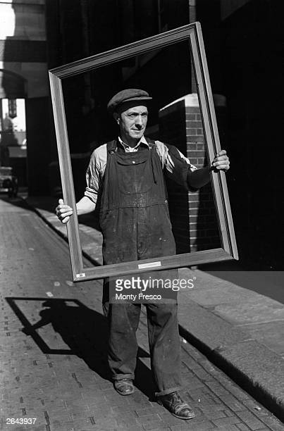 A Royal Academy workman taking a frame into the gallery on the first day of the Summer Exhibition in London
