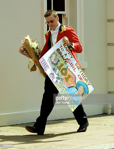 Royal aide acrries a birthday banner for The Queen Mother during celebrations to mark her 101st birthday August 4 2001 in London
