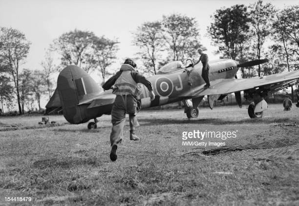 2nd Tactical Air Force, 1943-1945, A pilot of No. 175 Squadron RAF scrambles to his waiting Hawker Typhoon Mark IB at B5/Le Fresne-Camilly, following...
