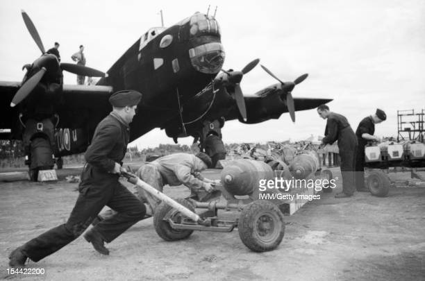 Royal Air Force Bomber Command, 1942-1945, Armourers wheel a trolley of 1,000-lb MC bombs into position for hoisting into Handley Page Halifax Mark...