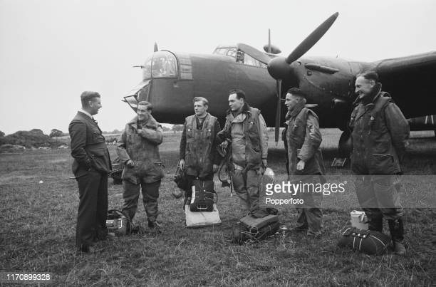 A Royal Air Force bomber crew receive last minute instructions from their Wing Commander at a Bomber Command station prior to boarding their...