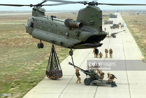 Royal Air Force CH-47 Chinook helicopter hooks up two pallets of ammunition and a 105-mm light field gun from the 29 Commando Regiment of the Royal...