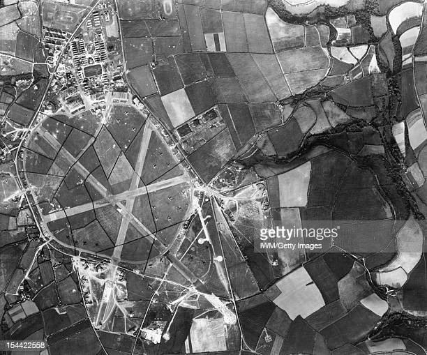 Royal Air Force Coastal Command 19391945 Vertical aerial view of RAF St Eval Cornwall Two badlydamaged hangars and numerous bomb craters around the...