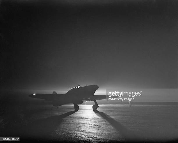 Royal Air Force Fighter Command 19391945 A Hawker Hurricane Mark I night fighter of No 85 Squadron RAF taxiing by the light of a flare at Debden...
