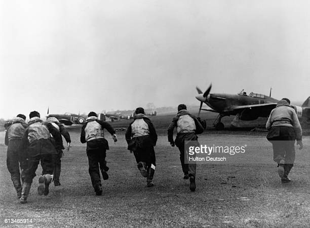 Royal Air Force fighter pilots of No 601 Squadron based at RAF Tangmere scramble to their Hawker Hurricane MkI fighters circa November 1940
