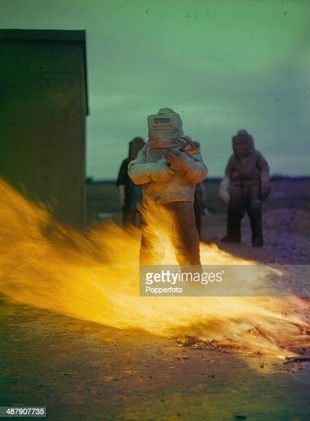 1943 Royal Air Force Fire Fighting School US soldiers clad in asbestos lined suits walking through fire February 1943