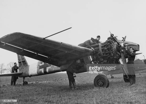 Royal Air Force groundcrew technicians of No1426 Flight RAF and known as the Rafwaffe examine the engine and propeller on captured Nazi Luftwaffe...
