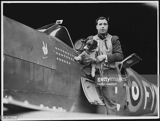Royal Air Force Lieutenant Stanley Lock by his plane with his dog an aerial mascot Lock's plane is marked with a V for victory crest and the number...