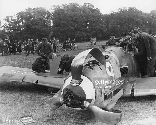Royal Air Force men examine a Messerschmitt 109 which crashlanded in Windsor Great Park after a failed attack on two British Anson aircraft The pilot...