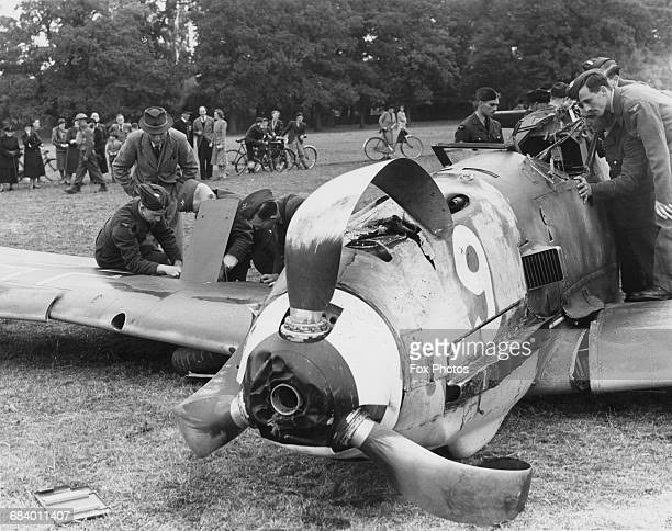 Royal Air Force Maintenance Unit personnel examine the wreckage of a Messerschmitt BF 109E1 of Jagdgeschwader 7 fighter wing of the German Luftwaffe...