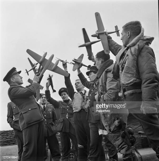 Royal Air Force pilots from No 253 Squadron hold model airplanes used for instructional purposes during an aircraft recognition training lesson at a...