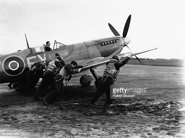 Royal Air Force pilots push a Spitfire fighter plane on a muddy airstrip