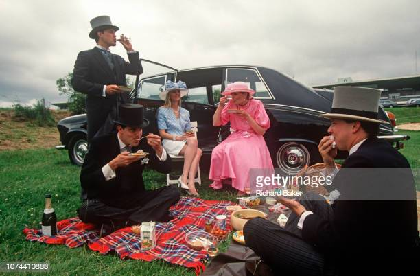 Royal Ascot racegoers picnic on the grass of an event car park, on 18th June 1992, in Ascot, England. Trays of food and two bottles of Champagne have...